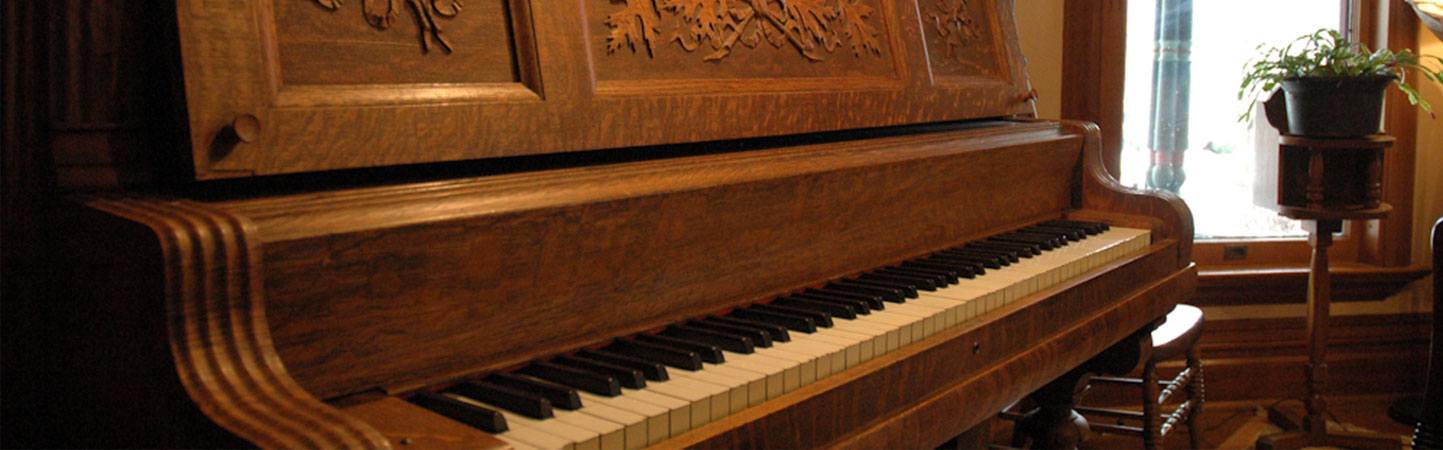 Angled view of keys of a 1908 Upright Piano with ornate wooden carving in a parlor with a window.