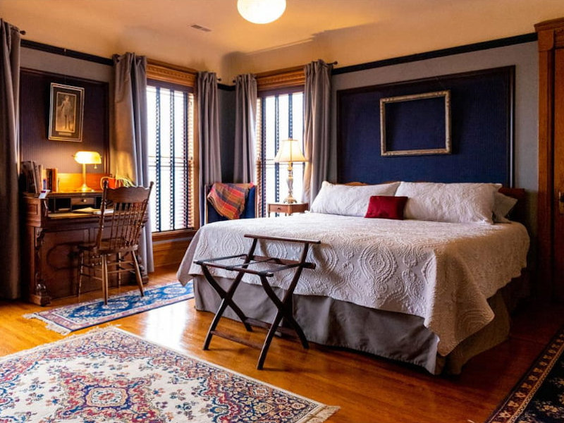 Masculine bedroom with muted blue walls that offset menswear fabric panels and silver bed coverings.