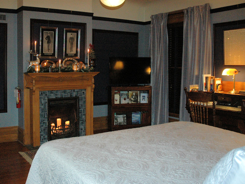 King bed faces both Victorian Fireplace lit with pillar candles, and flatscreen tv at Stuart Avenue BnB