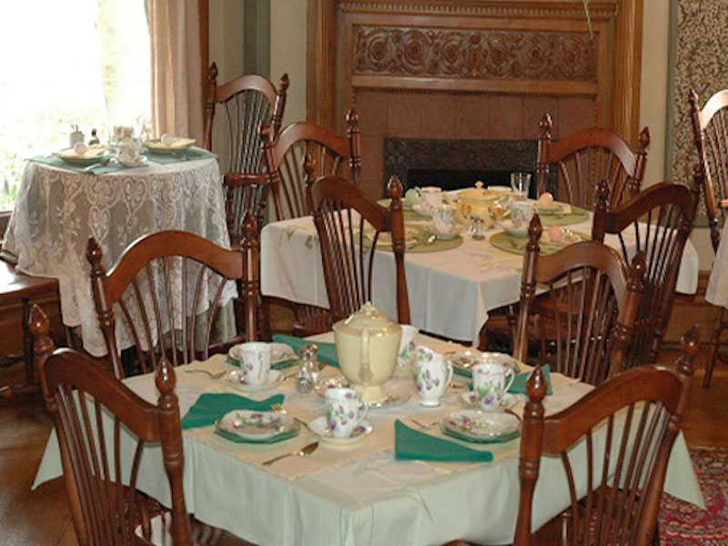 4-top tables draped with white linen tableclothes, and set with fine china, for a bridal shower at Stuart Avenue BnB
