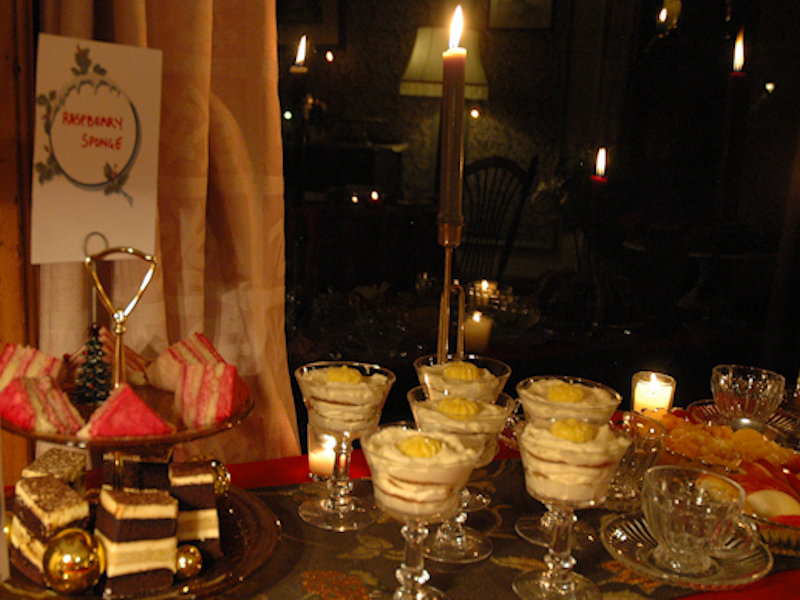 Candles light holiday desserts in crystal goblets and platters including lemon ginger mousse, raspberry cream tort, and fresh citrus