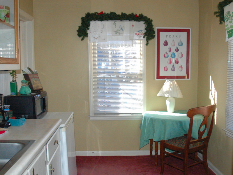 Round table and chair tucked to the wall in a small room with two double-hung windows.