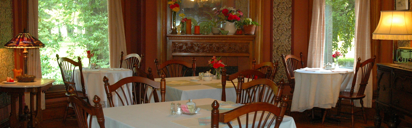 Tables of 2 and 4 set for breakfast with white linen on sunny morning at Stuart Avenue BnB