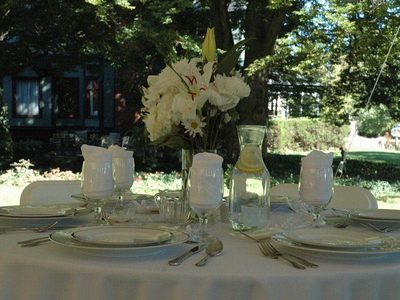 Outdoor table set in a garden,under a tent with white linen, fine china, water glasses and bouquet of fresh white flowers,