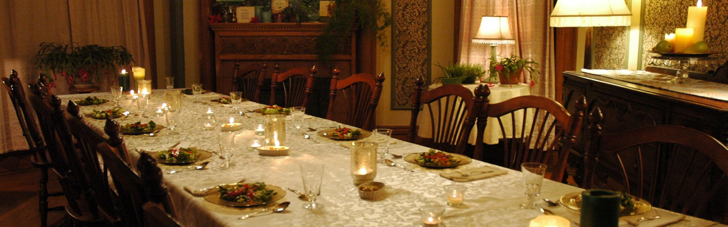 Table for 12 with creamy damask table cloth and first course of fresh green salad at elegant holiday dinner party