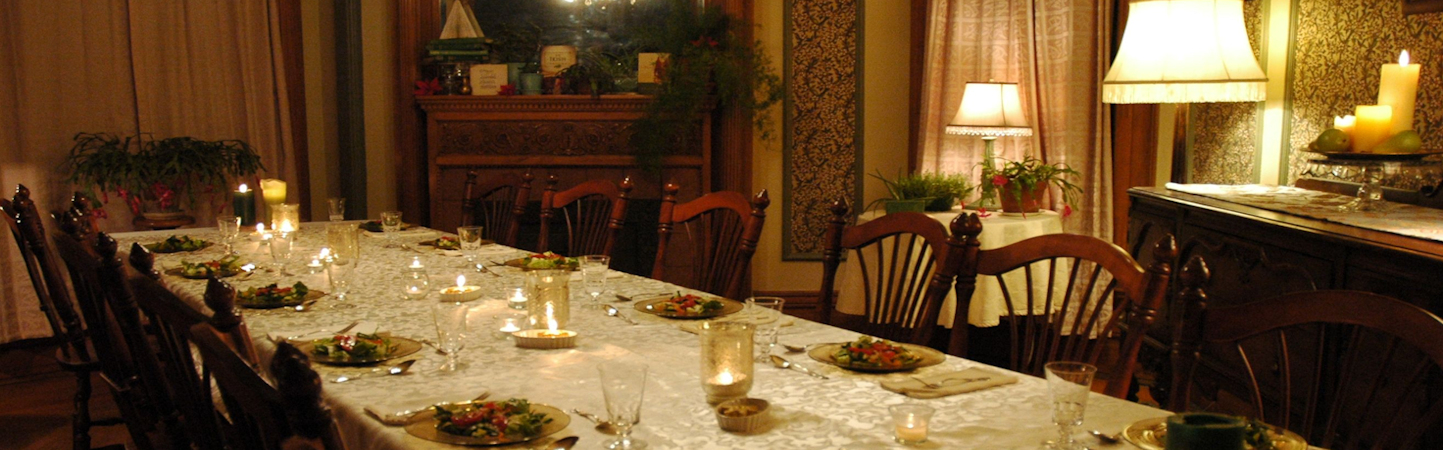Table for 12 set with creamy damask table cloth, candles, and plates of fresh green salad.