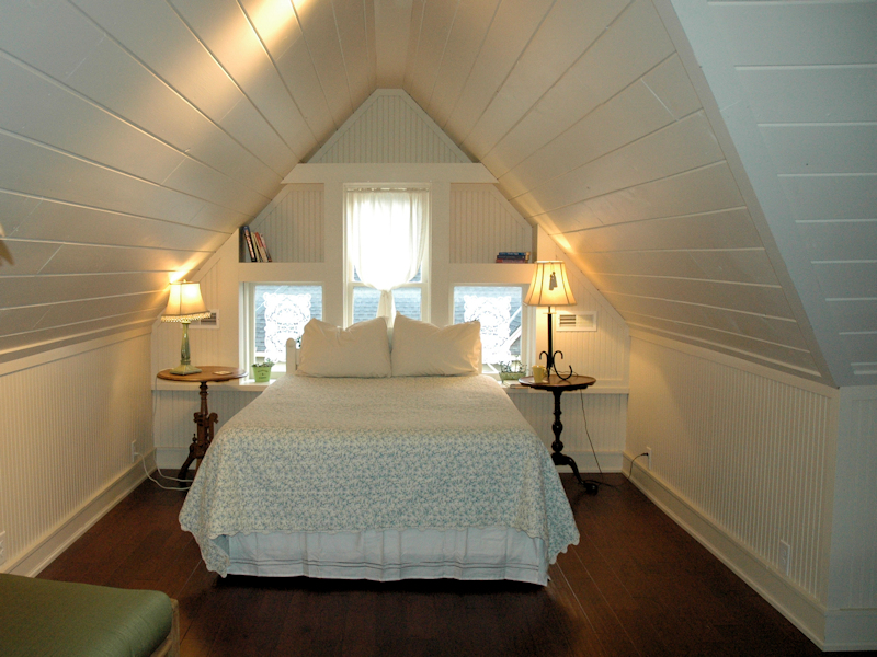 Queen bed nestled in third floor alcove with gabeled ceilings, two night stands, and three decorative windows.