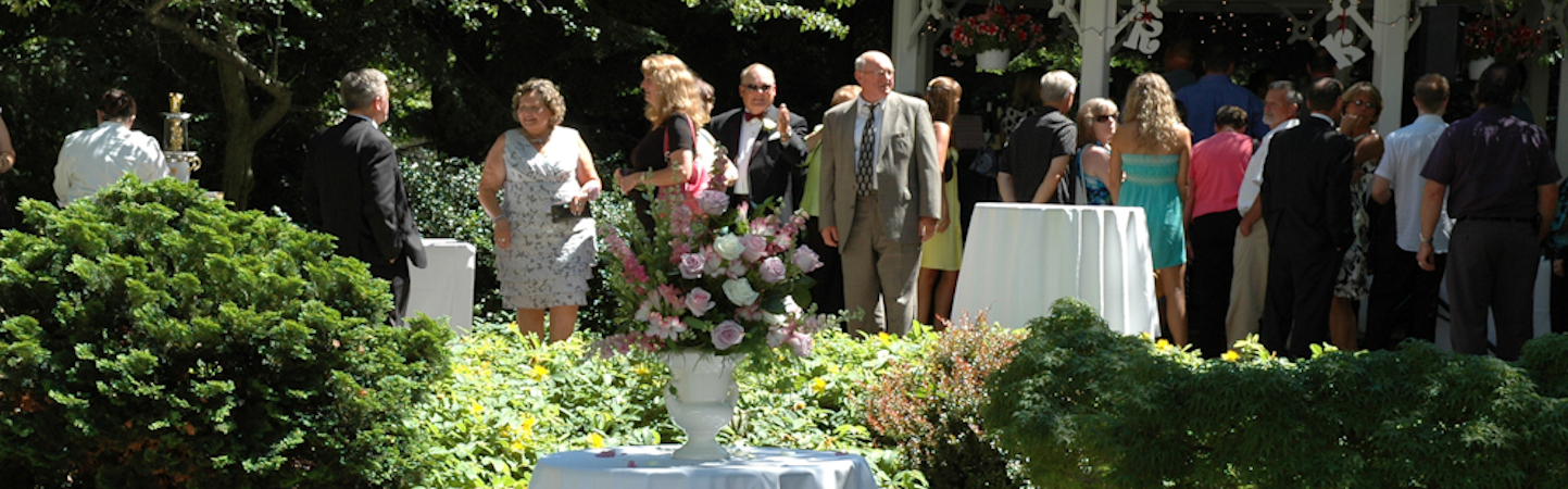 People gathered in lush gardens with white linen tables at Stuart Avenue BnB