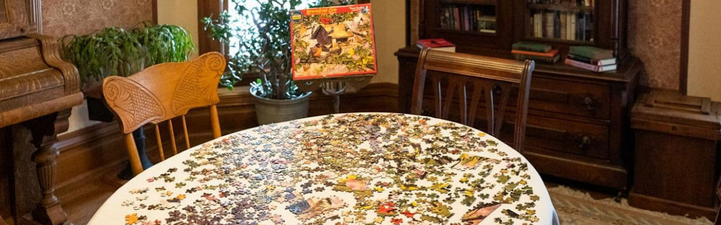 Jigsaw puzzle on parlor table with chairs and box displaying the finished picture.