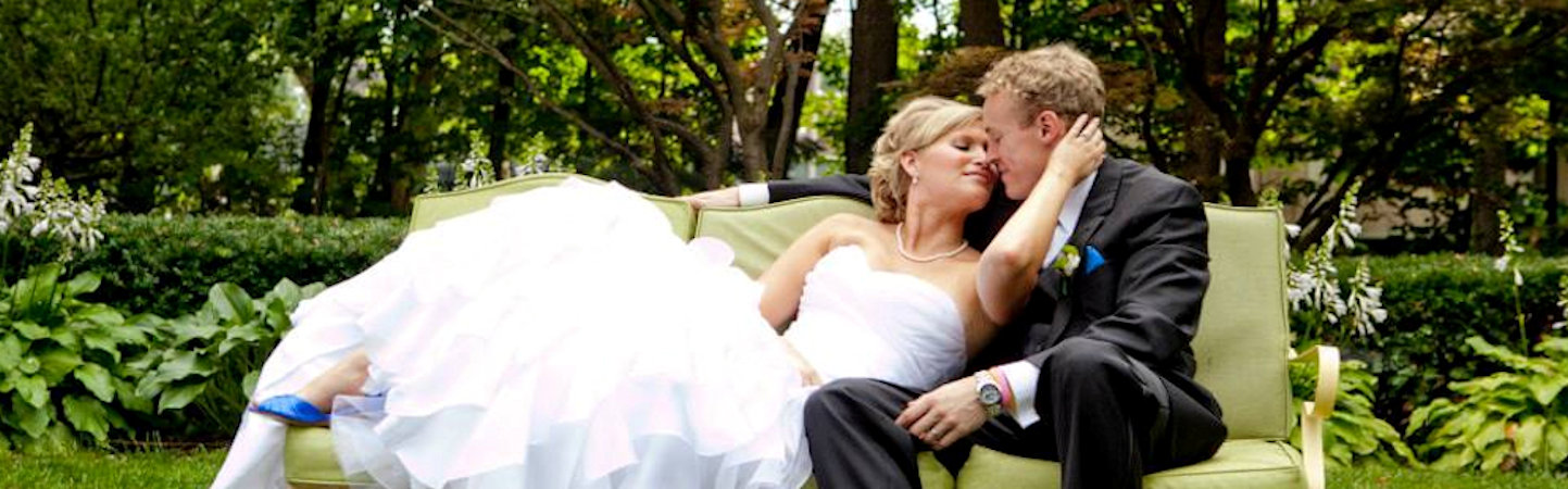 Bride and groom share a kiss on green couch in lush garden at Stuart Avenue BnB.