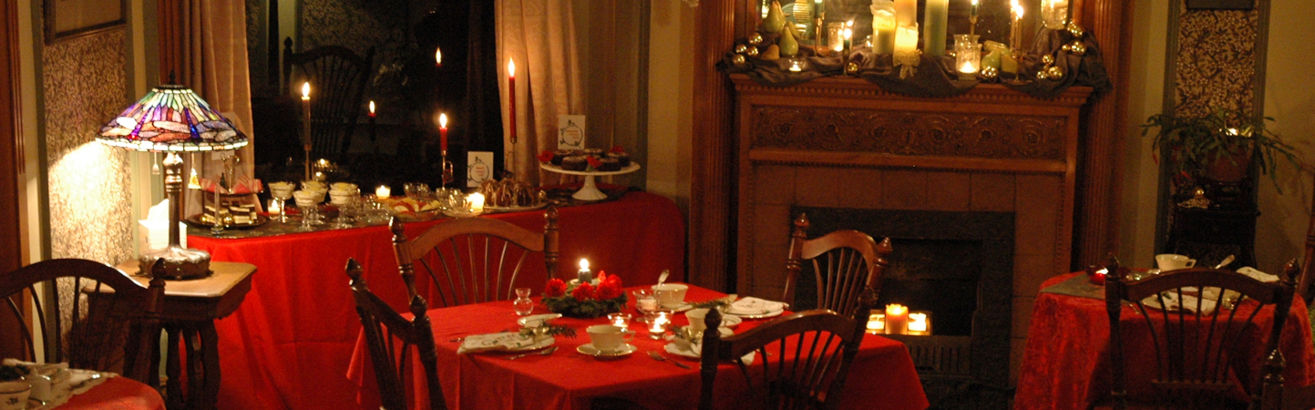 Victorian parlor at night bathed in candlelight and set for Christmas Tea with red tables, greenery, fine china and holiday linens.