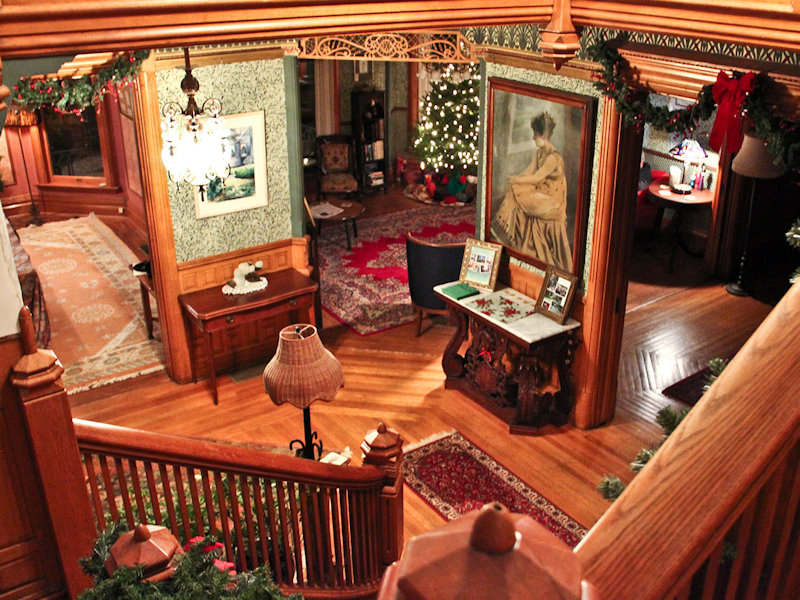 View from stairs into three Victorian parlors decorated with Christmas greenery, holly berries, and bows, with Christmas tree in background
