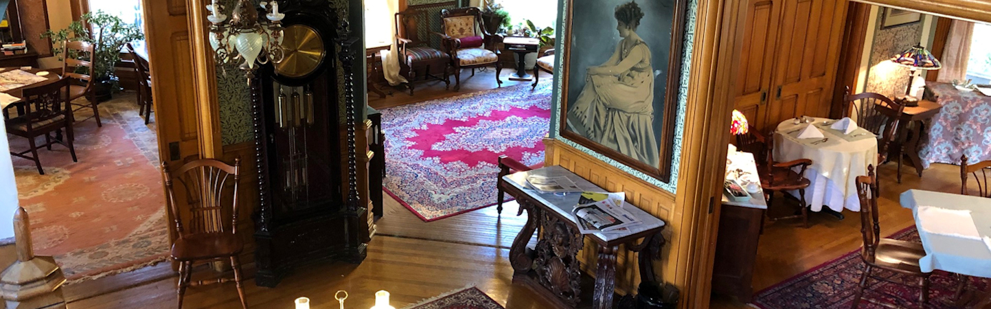 View from stairs into three Victorian parlors with Antique Grandfather clock and painting of woman from the 1920's.